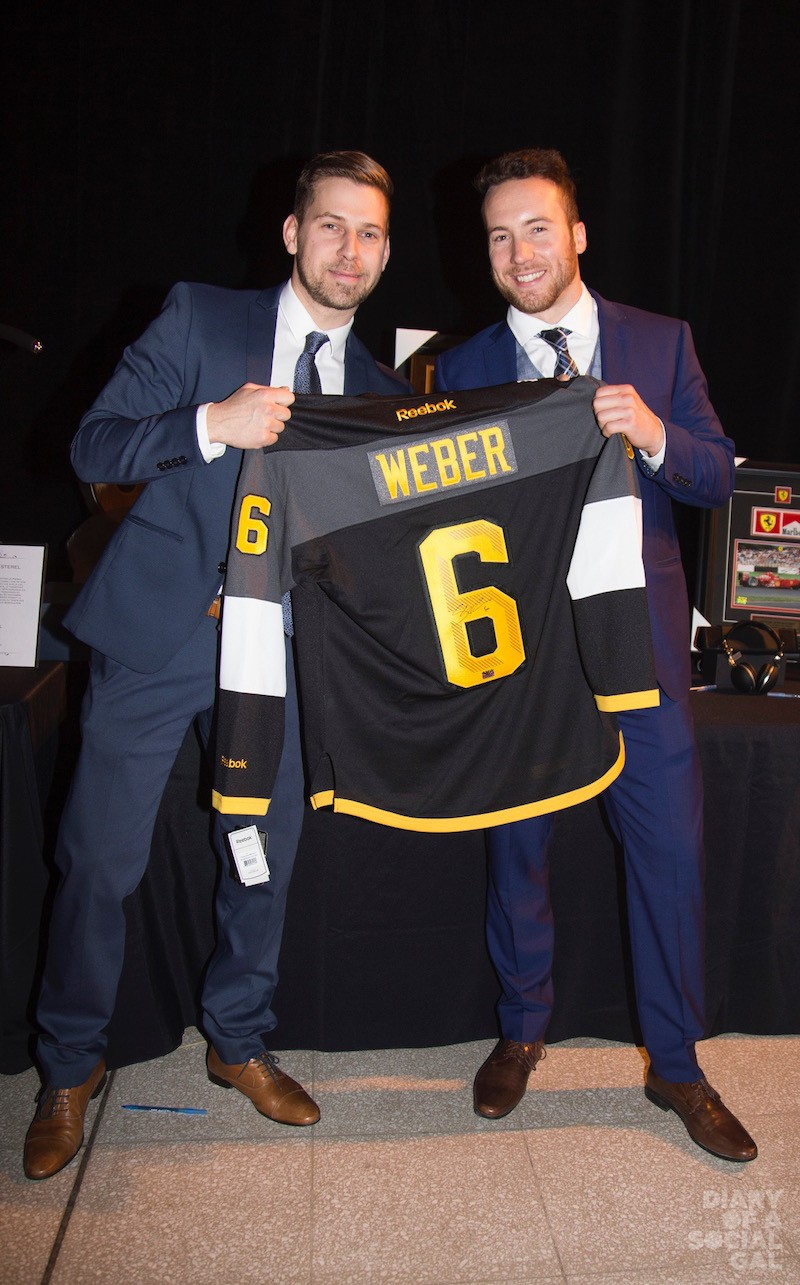 SPORTS STUFF SELLS: Guests KEVIN CORDWIN and DAVID COMEAU get into the silent auction spirit.