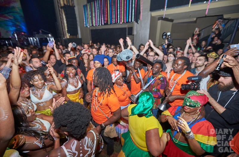 TROPICAL SHAKEUP! Members of the Rara Soley Troup (in orange tees) and 100 Lux dancers (in kini tops and body paint) join the crowd for another amazing KANAVAL!