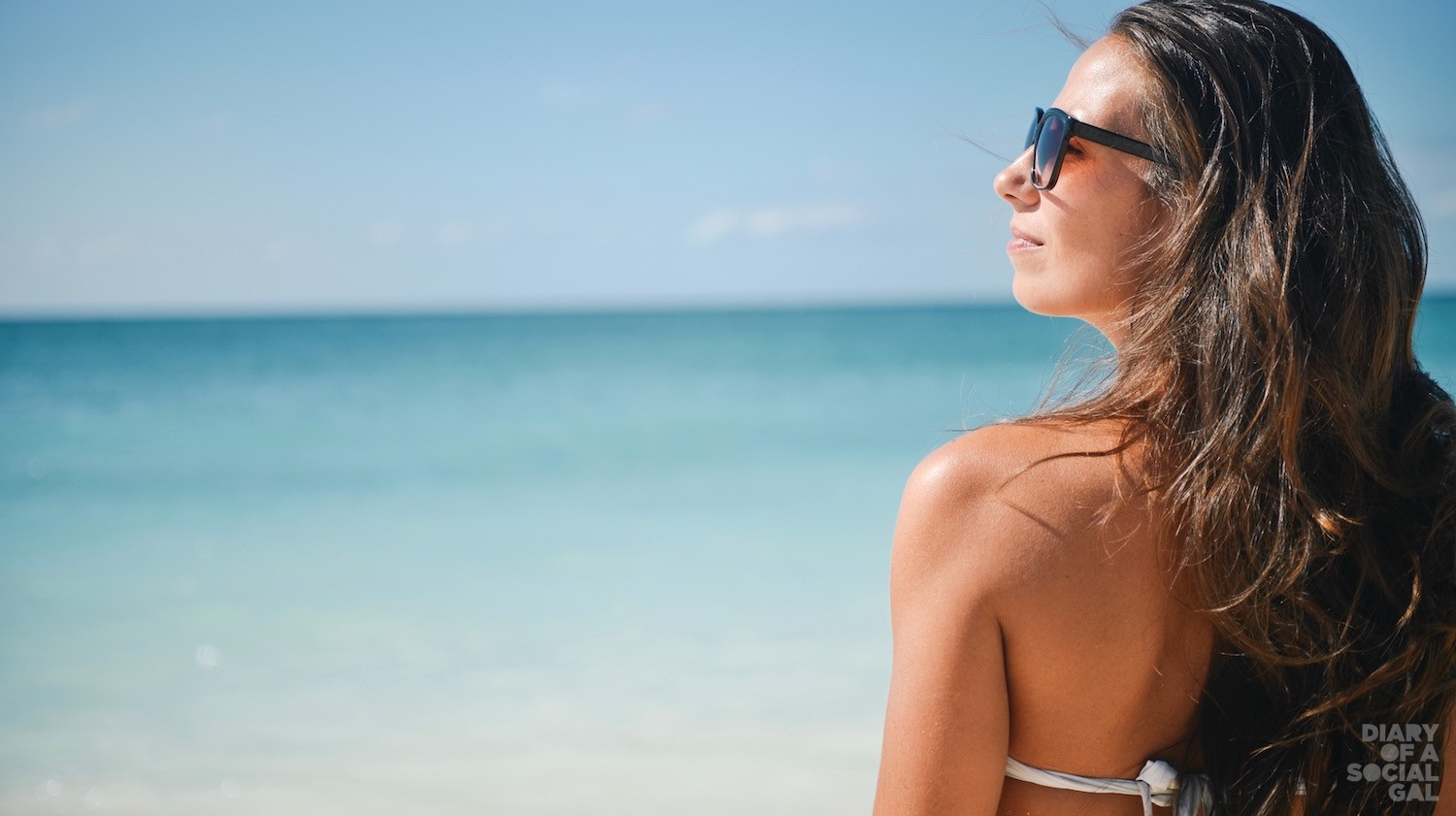 Girl In Bikini Wearing Sunglasses On A Beach Looking At The Sun (1)